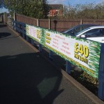Temporary printed promotional banner secured to a fence